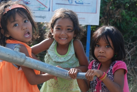 Children in a Cambodian village using the pump well built by Lotus Outreach.
